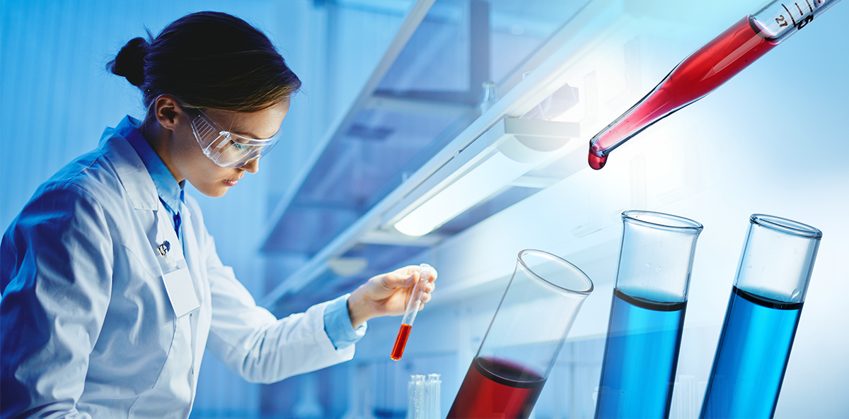 scientist looks at red vial with red vial and two blue vials in front
