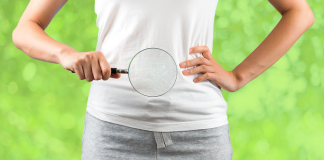 woman holds magnifying glass in front of stomach over green background