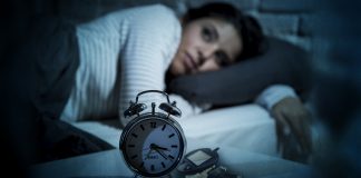 Woman lying in bed awake, alarm clock