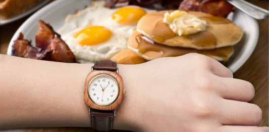 hand with watch over plate with breakfast foods