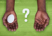 two hands over green background with one holding an egg and a question mark in between