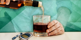 drinking with diabetes; hand pouring liquor into glass with diabetes monitor over green background