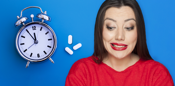 woman grimacing with pills and alarm clock over blue background