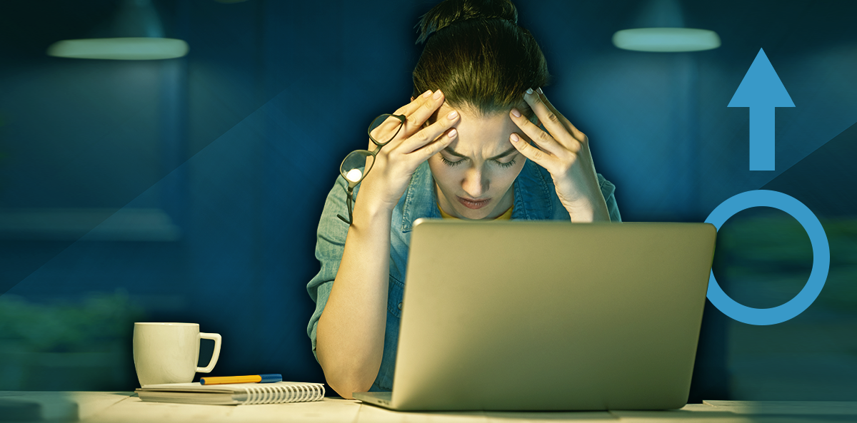 woman working at laptop, head in hands, working too many hours leads to increased diabetes risk in women