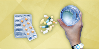 hand grasping water next to pills over yellow background
