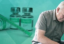 man with head in hands sitting beside insulin; insulin resistance